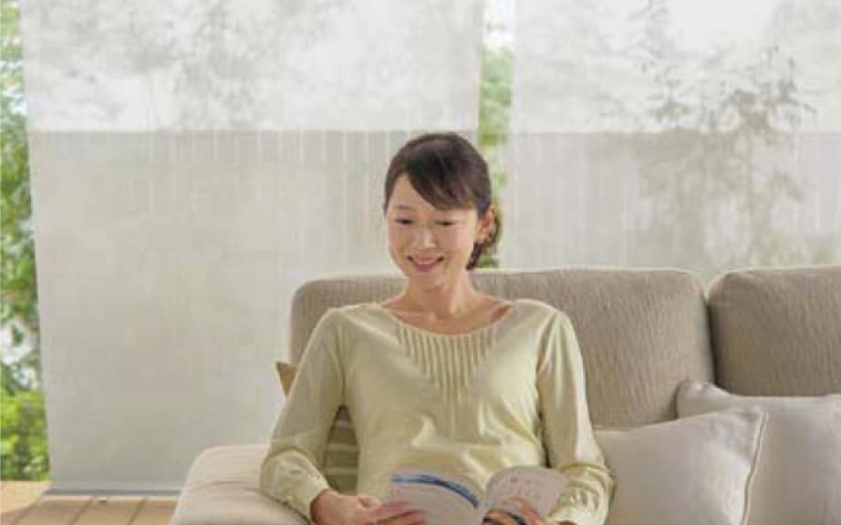シェードをすることでエアコンを効率化し夏でも快適に過ごす女性